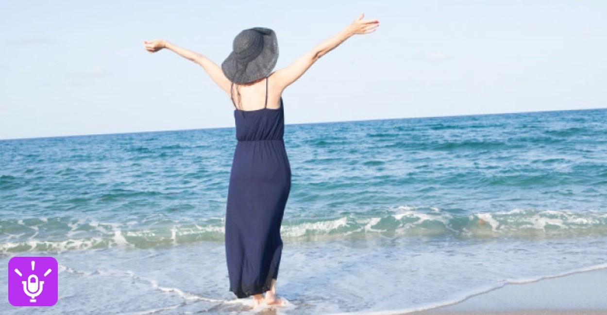 海に向かって両手を広げる女性